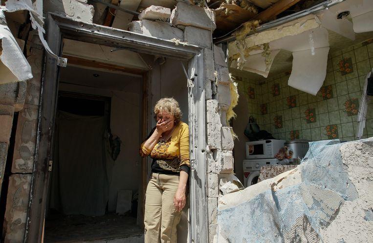 Een inwoner van een dorp nabij Donetsk, in Oost-Oekraïne, bekijkt de schade van haar huis na gevechten. Beeld EPA