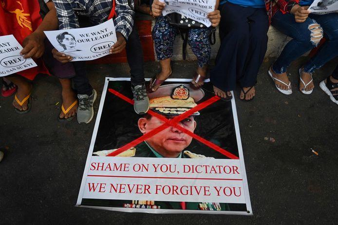 Demonstranten staan op een afbeelding van de militaire machthebber van Myanmar, Min Aung Hlaing. Archiefbeeld van februari van dit jaar.