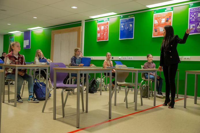 Eerste fysieke lesdag weer op de Notre Dame in Ubbergen. Hier bij de eersteklassers zitten de kinderen ruim uit elkaar en staat de docente achter de rode lijn om afstand te houden.