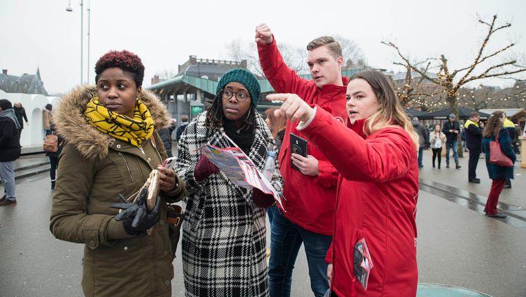 Mbo'ers Luuk en Linde (in rode jassen) wijzen toeristen de weg op het Museumplein Beeld Charlotte Odijk