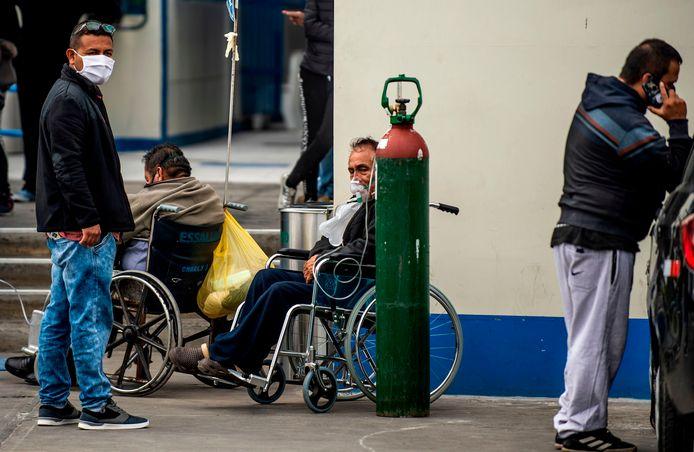 Mensen wachten op hulp bij een ziekenhuis in Lima. Een man in een rolstoel krijgt zuurstof via een grote fles die naast hem staat.