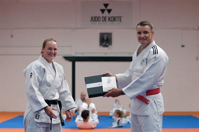 Hester Hoogland (links) geeft haar eerste boek aan Olympisch kampioen Mark Huizinga.