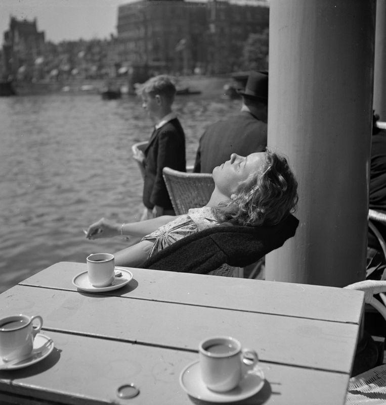 Terras bij Amsterdam Centraal Station. 'Op een terras kun je tonen dat je niet hoeft te werken en dat het je goed gaat.' Beeld ANP / Maria Austria Instituut