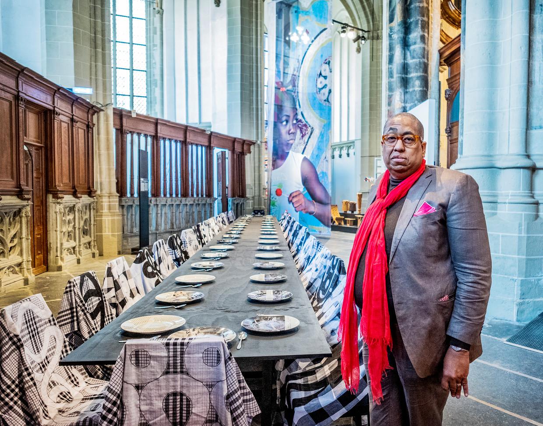 John Leerdam. Op de foto de door Surinaamse kunstenaar Marcel Pinas gemaakte Offertafel voor de 38 mensen die in 1986 gedood werden in het marrondorp Moiwana. Daarachter een portret van Desi Bouterse die opdracht gaf rebellenleider Ronnie Bruinswijk in het betreffende dorp te arresteren. Die werd niet gevonden waarop de soldaten van Bouterse minstens 38 dorpelingen afslachtten.