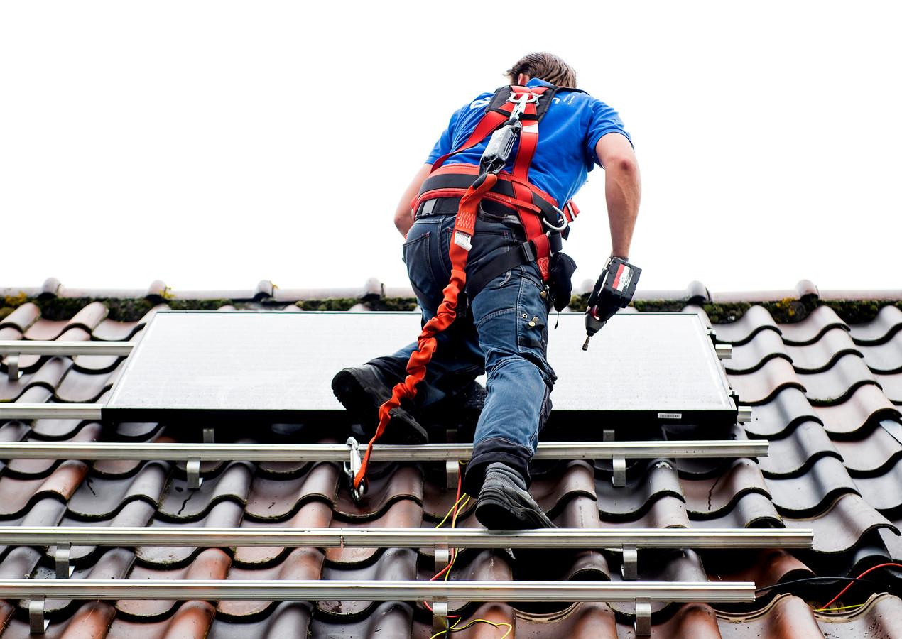 Foto ter illustratie. Een monteur plaatst zonnepanelen op het dak van een woonhuis.