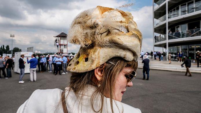 Waregem Koerse: Kunstenares Iryna Akimova uit Ursel heeft uit een boomstam een hoed gesculpteerd, en die afgewerkt met pluimen van haar Siberische Oehoe-uil.