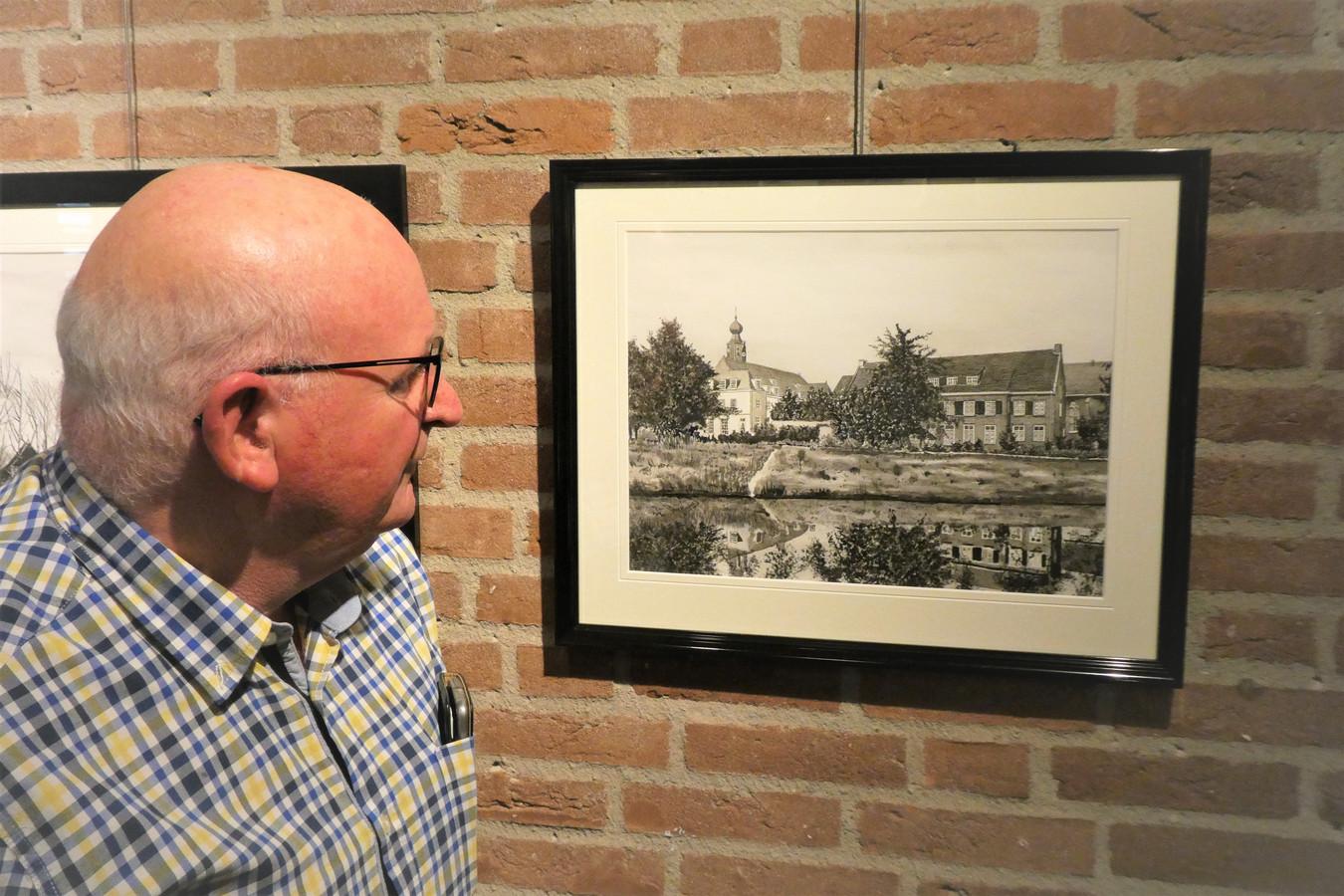 Wim Maas bij een van zijn 'troetelkindjes', de pentekening van Nieuw-Herlaer met de mooie waterspiegeling in De Dommel.