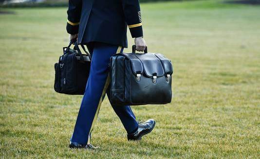 Een militaire assistent droeg de nucleaire tas toen Donald Trump vandaag het Witte Huis verliet.
