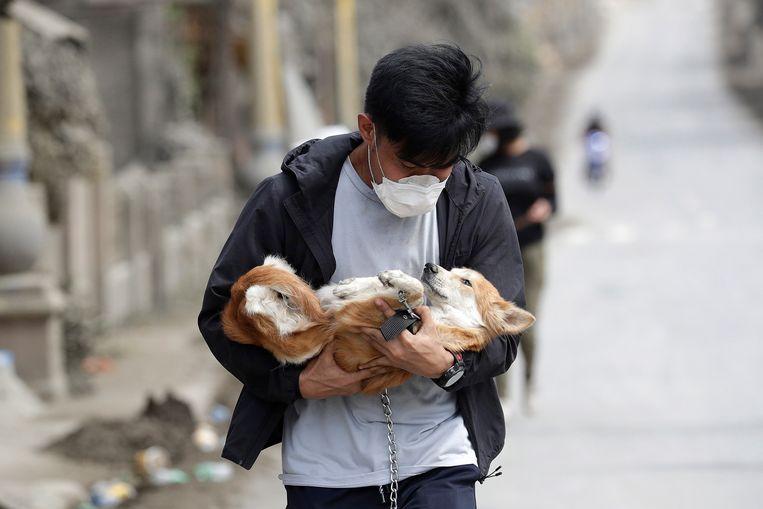 Een vrijwilliger draagt een hondje op zijn arm.
