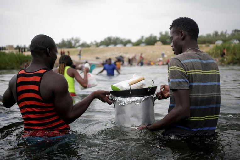 Haïtianen waden met hun spulletjes door de rivier. Beeld REUTERS