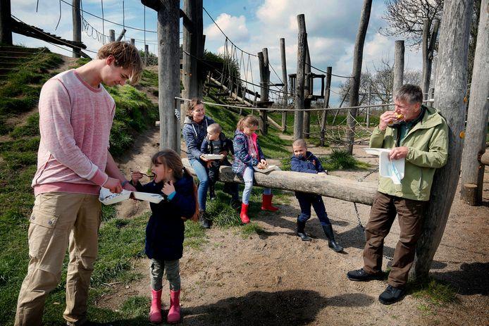 Tristan Borst (links) en zijn moeder Ingrid eten pannenkoeken met de kinderen. Buurman van het GeoFort, Bart Pijnenburg (rechts), eet ook een hapje mee.