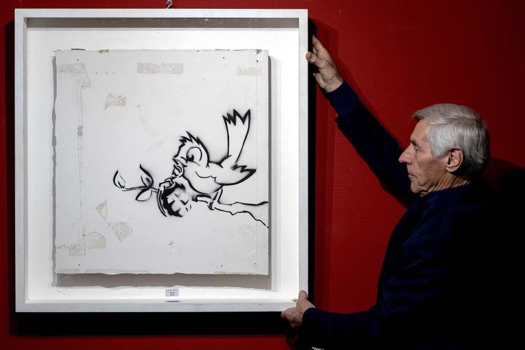 An employee of the auction house Hessink presents a graffiti painting 'Bird with Grenade' made by artist Banksy on November 26, 2020 in Zwolle. - Auction house Hessink is auctioning the art work and expects a price between 200,000 and one million euros. (Photo by Sander Koning / ANP / AFP) / RESTRICTED TO EDITORIAL USE - MANDATORY MENTION OF THE ARTIST UPON PUBLICATION - TO ILLUSTRATE THE EVENT AS SPECIFIED IN THE CAPTION Beeld AFP