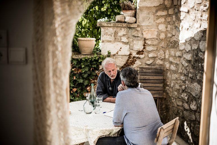 ► Stefan Hertmans thuis in gesprek met journalist Rik Van Puymbroeck. 'Het geheime wapen van talent is dat je je er nooit op moet laten voorstaan. Je hebt nooit het recht om arrogant te worden.' Beeld Diego Franssens