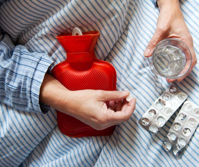 Een vrouw in bed neemt paracetamol Beeld ANP XTRA
