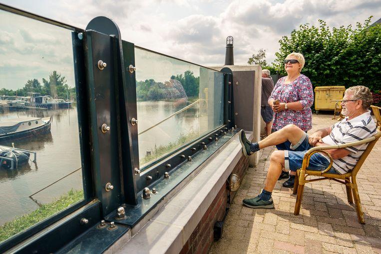 Vrijwilligers van Watersportvereninging Wansum in Neer, Jacqueline Korsten en Max Touw (stoel) zitten tevreden achter de glazen waterkering die er pas sinds februari staat. Beeld Maikel Samuels