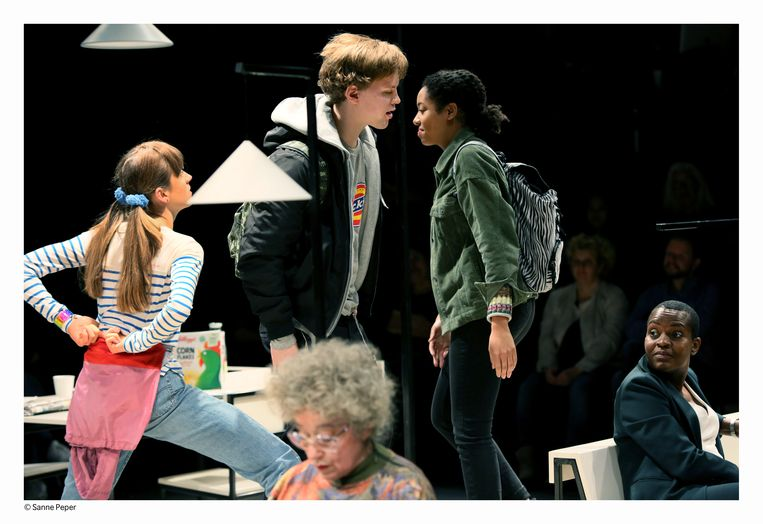 Scène uit 'Onze Straat', met rechtsonder verteller Romana Vrede.  Beeld Sanne Peper
