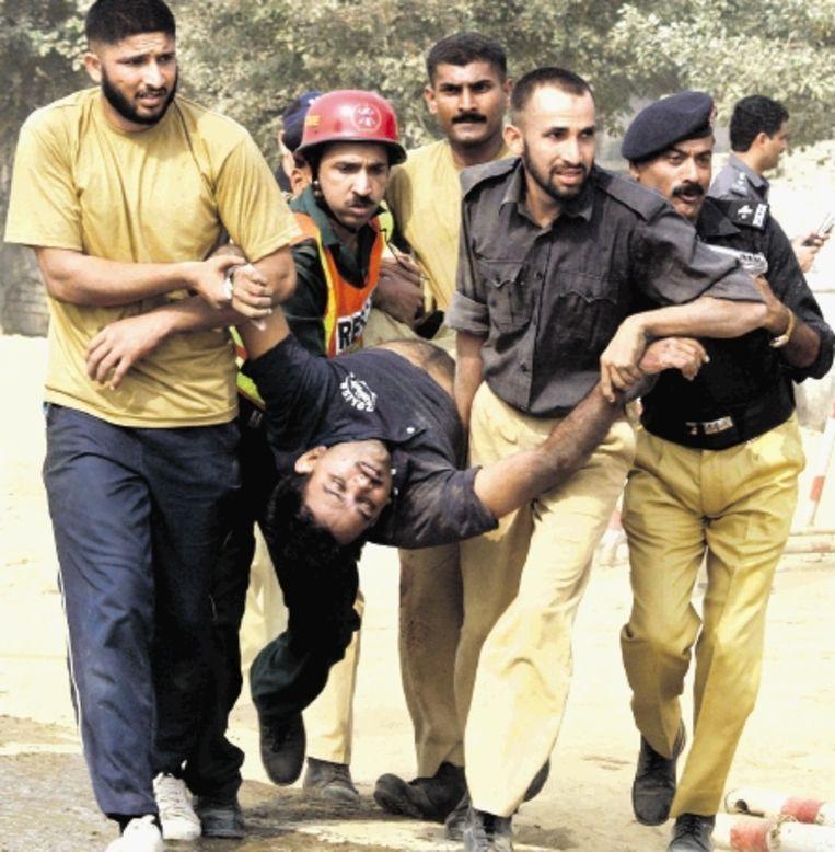 Pakistaanse politiefunctionarissen dragen een gewonde collega weg na een aanslag bij de opleidingsschool voor commando?s in Lahore. (FOTO AFP) Beeld