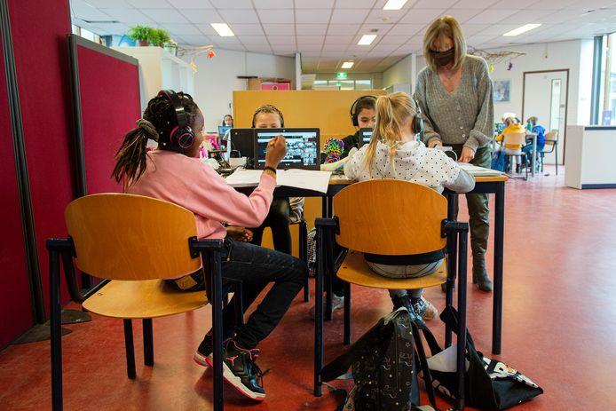 Leerlingen van De Boomgaard in de schoolaula aan het werk. Met koptelefoons op volgen ze online de les van hun eigen leerkracht. De begeleiding is letterlijk bij de hand.