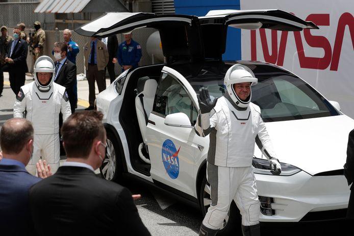 Astronauten van de NASA klaar voor vertrek bij een Tesla Model X die ze naar de lanceerinstallatie van Kennedy Space Center in Cape Canaveral, Florida zal brengen. Deze astronauten bemanden op 27 mei vorig jaar een testvlucht van SpaceX naar het International Space Station. Links op de foto, met het zwarte colbert: SpaceX CEO Elon Musk