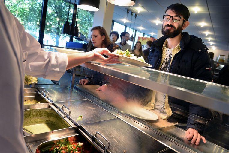 Een student krijgt zijn maaltijd in de kantine van de Radboud Universiteit. Beeld Marcel van den Bergh / de Volkskrant