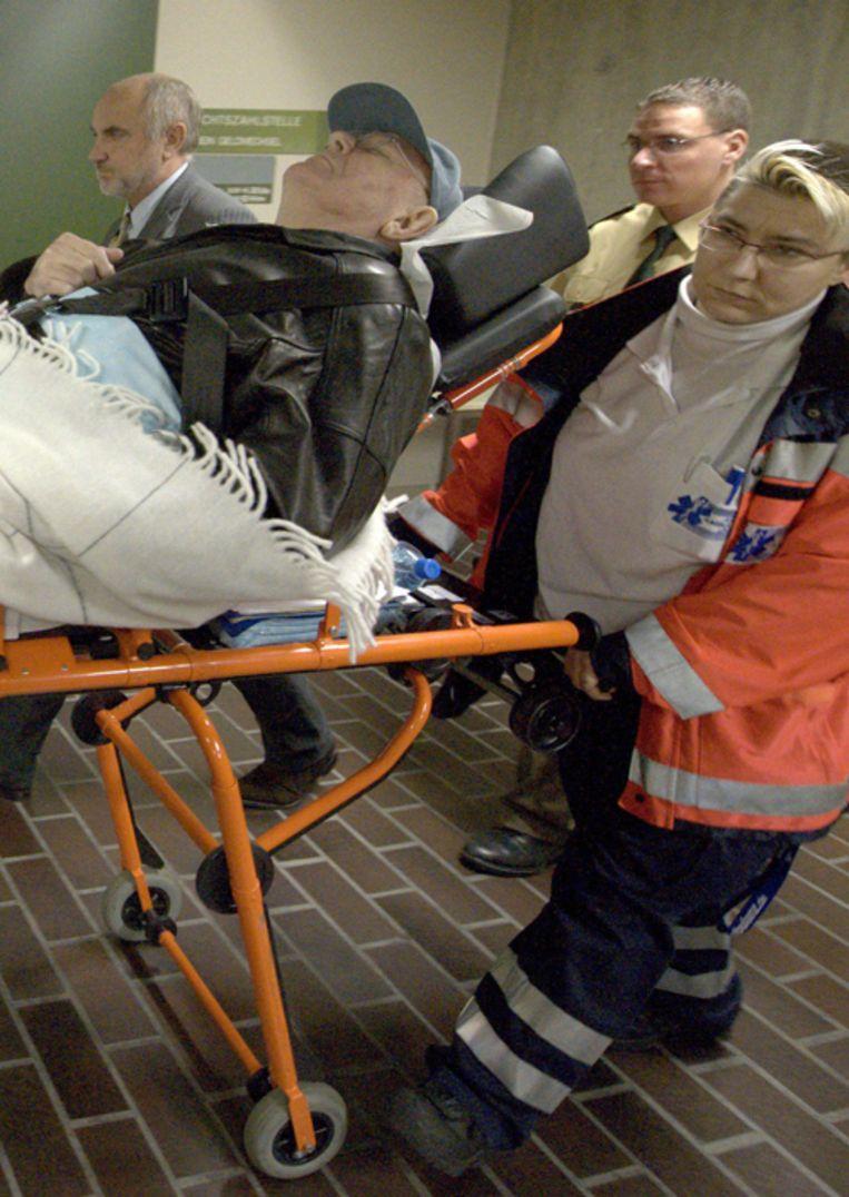 De van oorlogsmisdaden verdachte John Demjanjuk wordt na de eerste zittingsdag de zaal in München uitgereden. Ook vandaag arriveerde hij per brancard. Foto EPA Beeld