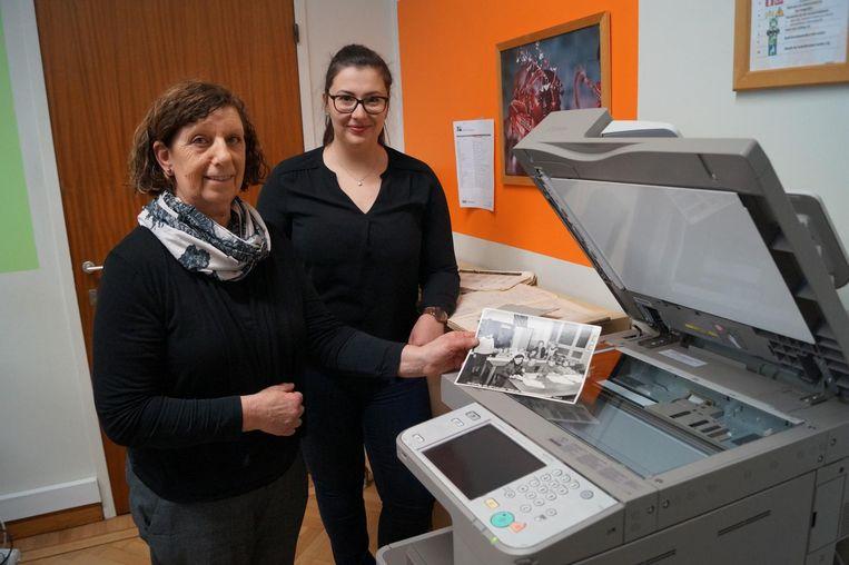 Conciërge Herlinda Casteleyn en leerkracht Ruth De Rammelaere scannen oude foto's in voor de expositie.