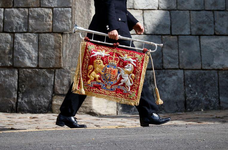 Een militair op weg naar de repetitie in Windsor Castle draagt een bugel met de koninklijke vlag.  Beeld REUTERS