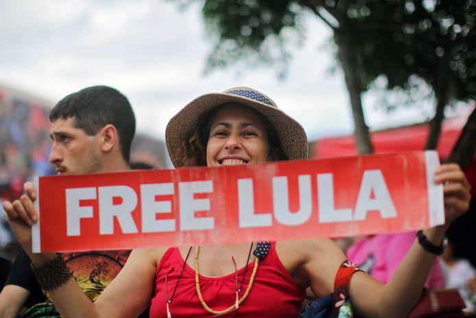 Een vrouw houdt een bordje omhoog waarop 'Bevrijd Lula' staat.