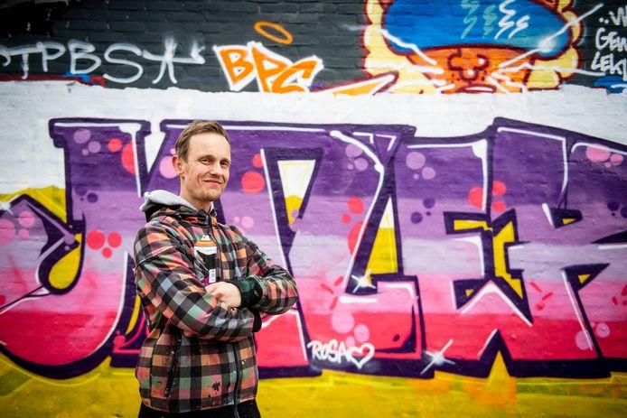 """Tim Bergboer bij zijn graffiti op de Duiventil. In maagdelijk wit, met hartje, het bewijs dat ook zijn 4-jarige dochter Rosa mee schilderde. ,,Ik heb haar een graffitipistool gegeven. Dat is heel leuk voor jonge kinderen. Die vinden het moeilijk om op zo'n spuit te drukken"""", aldus Bergboer."""