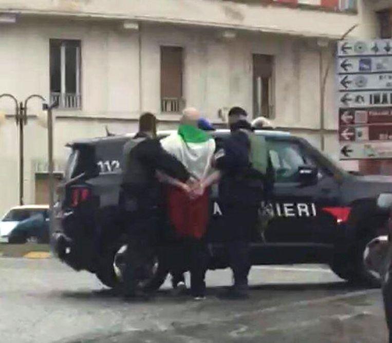 Schutter Luca Traini wordt gearresteerd door de Italiaanse politie op 3 februari in Macerata.  Beeld REUTERS