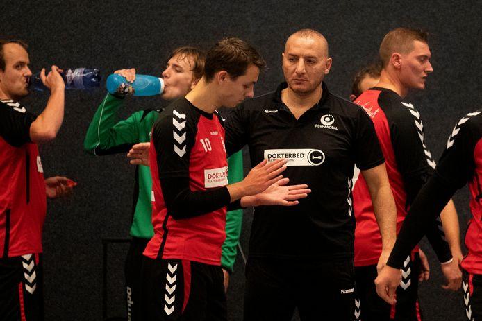 PSV-coach Saji Al Mahamed  (zwarte shirt)luistert naar een van zijn spelers.