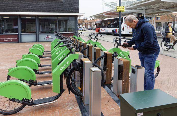 De verslaggever reserveert met zijn mobiele telefoon een e-step bij de centrale bushalte in Waalwijk.