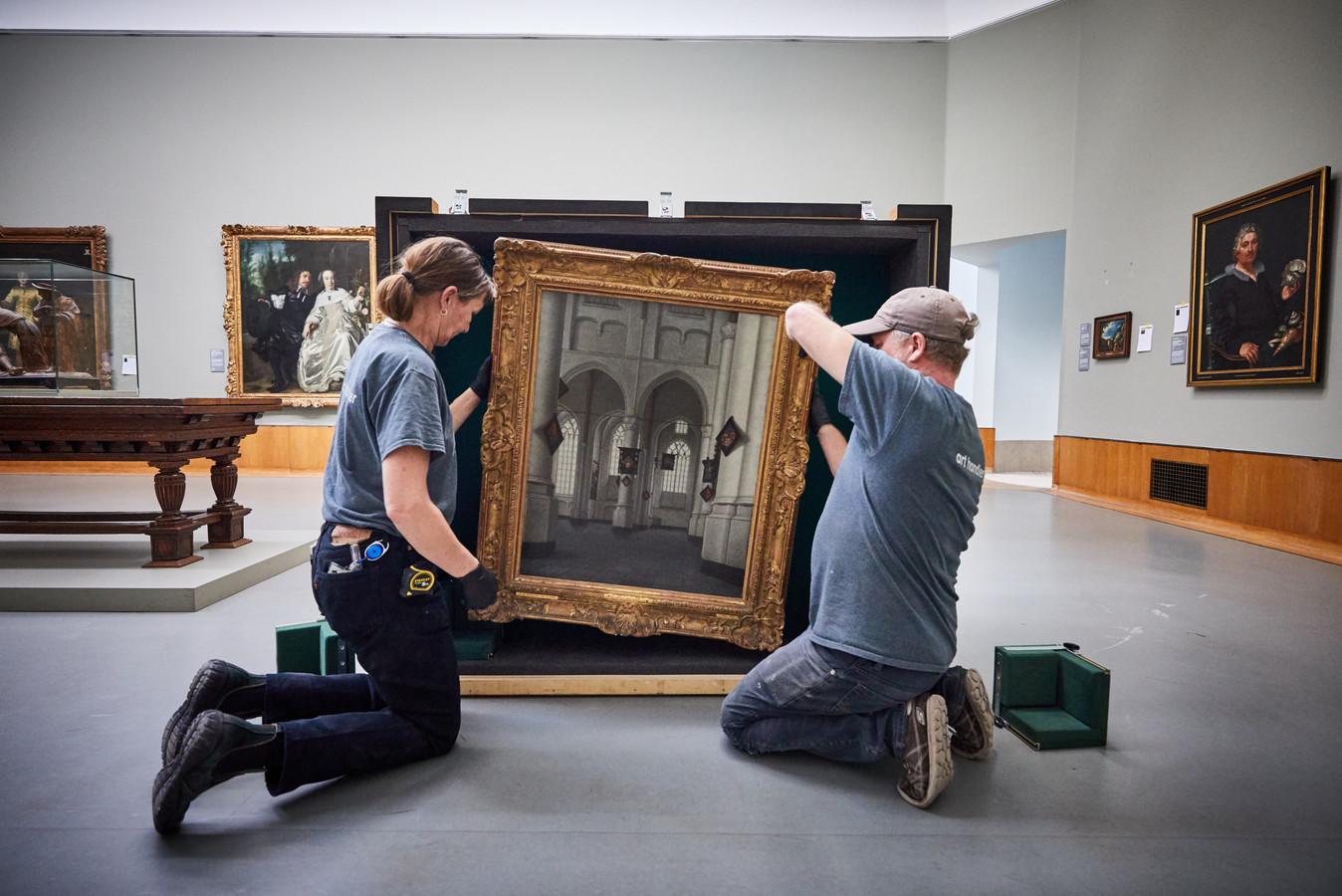 Art handlers Max Wijlacker en Leon Duenk stoppen een werk van Anthonie de Lorme in een verhuiskist.