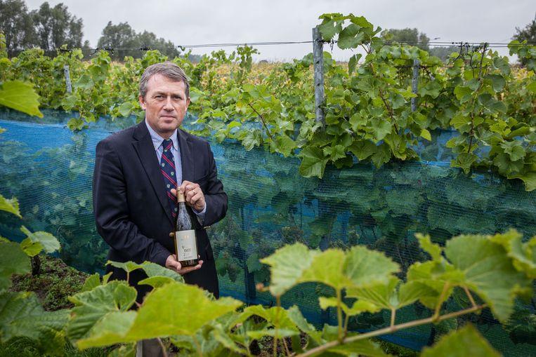 Lodewijk Waes met zijn winnende wijn tussen de druivenranken.