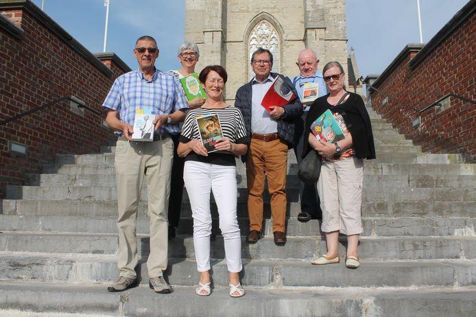 De leden van de Lennikse afdeling van het Rodenbachfonds kwamen samen aan de trap van de kerk van Sint-Martens-Lennik om gratis boeken uit te delen.
