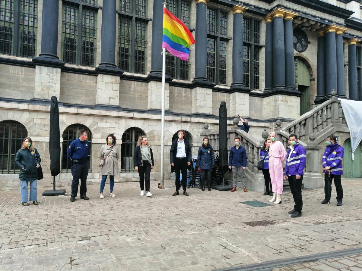 Een deel van het schepencollege, vertegenwoordigers van Casa Rosa en Unia verzamelen onder de regenboogvlag aan het stadhuis.