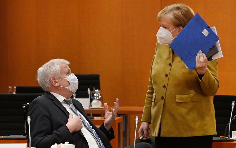 De Duitse bondskanselier Angela Merkel (R) praat met minister van Binnenlandse Zaken Horst Seehofer tijdens een kabinetsvergadering bij de bondskanselarij. Beeld AFP