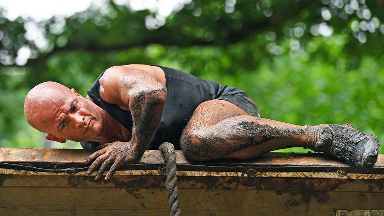 Een deelnemer aan Strong Viking klimt over een muur. Beeld Guus Dubbelman / de Volkskrant