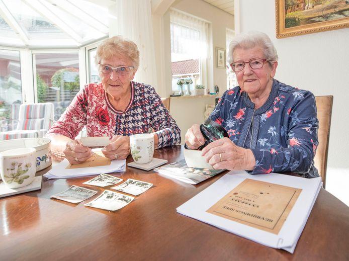 Nel de Kraker (links) en Sophie de Meij kijken naar oude foto's en het programmaboekje van het Bevrijdingsspel Ovezande waar zij in 1946 in mee speelden.