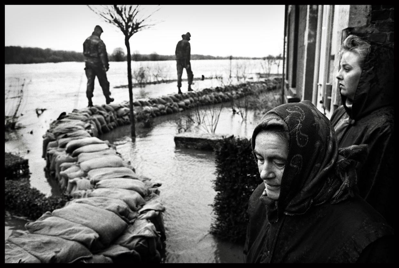 Militairen controleren in 1995 de zandzakken die Limburg voor nog grotere ellende moesten behoeden. Beeld Marcel van den Bergh/de Volkskrant
