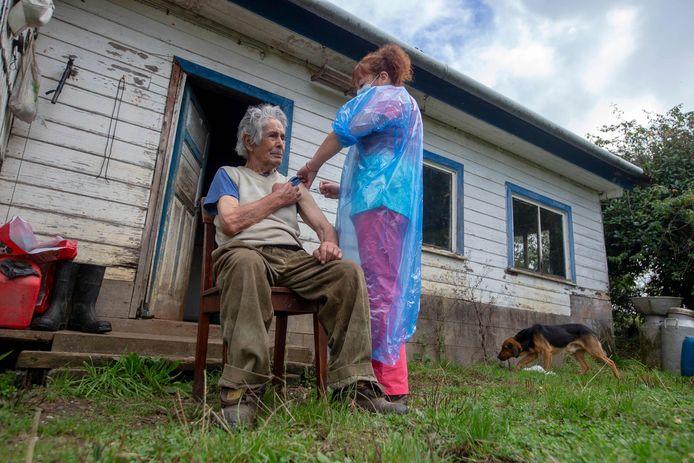Verpleegster Ximena Ampuero op bezoek bij een oudere man tijdens de vaccinatiecampagne in Chili.