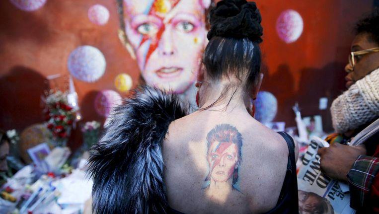 Een vrouw met een tatoeage van David Bowie bij een eerbetoon aan de overleden zanger in Brixton in Zuid-Londen Beeld reuters