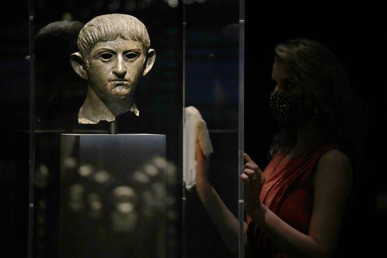 Een medewerker poetst het glas waarachter een bronzen kop van Nero tentoongesteld wordt. De expositie Nero, the man behind the myth toont een minder wreed beeld van de keizer dan we gewend zijn. Beeld AP