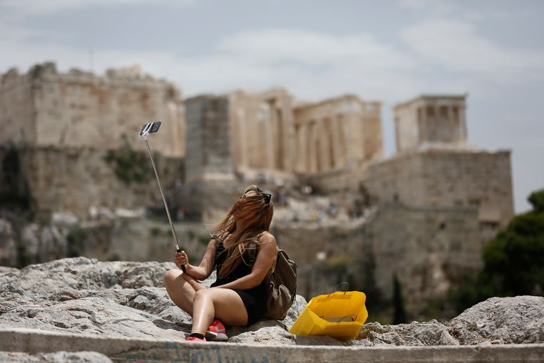 Een toeriste neemt een selfie voor de Akropolis in Athene. Beeld EPA