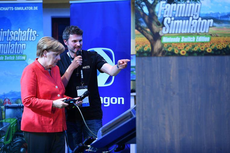 Duitse bondskanselier Angela Merkel speelt een landbouwspel aan de Nintendo-stand tijdens de gamesbeurs Gamescom in Keulen. Beeld AFP