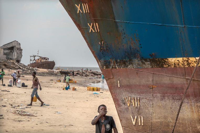 Het strand bij Praia Nova ligt bezaaid met scheepswrakken. Sommige worden in stukken gezaagd en verkocht als oud ijzer, andere moeten blijven liggen en doen dienst als golfbrekers bij hoogwater om de kust te beschermen.  Beeld Sven Torfinn