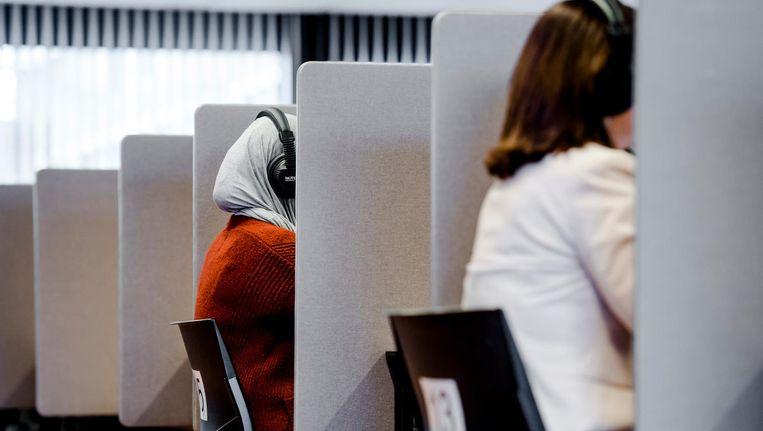 Een mevrouw maakt een inburgeringsexamen op een toetslocatie van Dienst Uitvoering Onderwijs. Beeld ANP