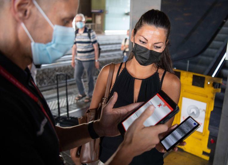 Passagiers op Station Roma Tiburtina tonen hun 'green pass'. Beeld Maurizio Brambatti/EPA
