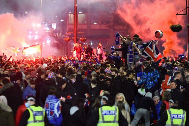 Politie houdt toezicht op de menigte die zich op George Square in het centrum van Glasgow verzamelde om de eerste Schotse titel van Rangers FC na tien jaar te vieren.  Beeld AFP