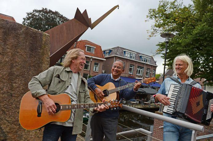Troubadour Peter Schoof bezingt Almelo bij beeld van Kop'ren Ko in de buurt van Café België. Hij wordt begeleid door Toon Faulhaber(m) Toon Lansink(r).